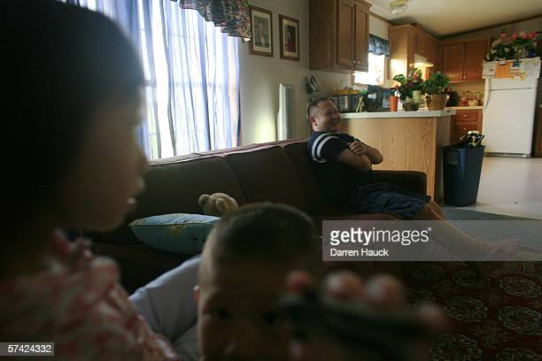 Lysauke Yang a Hmong immigrant right watches television as two of his five children play after he returned from the morning feeding of nearly 500...