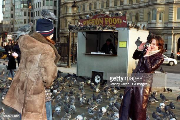 Lyuda Zezyulena has her photograph taken by Sveta Mudrakova who are Ukrainian tourists in front of Rayners bird seed stall in Trafalgar Square...