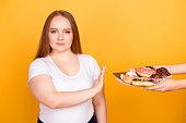 I'm against eating products containing fat! Will-powered woman wearing white tshirt is refusing to consume tasty delicious sweets on a plate, isolated on bright yellow background
