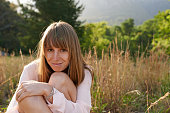 Candid portrait of a smiling young woman sitting in a field with forest in the background