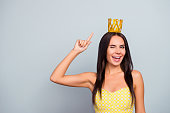 I'm queen of beauty! Where are my servants? Cheerful beautiful attractive pretty charming woman is pointing on the golden crown on her head and giving a wink, isolated on grey background, copy-space
