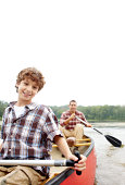 Portrait of a young boy enjoying a kayak ride with his father