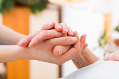 Nurse holding the hand of an elderly woman, showing sympathy and kindness.