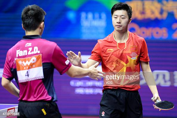 Ma Long of China shakes hands with Fan Zhendong of China during men's singles semifinal match on day eight of the 2015 World Table Tennis...