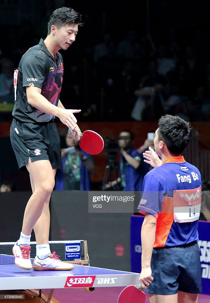 Ma Long (L) of China shakes hands with Fang Bo of China after winning men's singles final match on day eight of the 2015 World Table Tennis Championships at the Suzhou International Expo Center on May 3, 2015 in Suzhou, China.