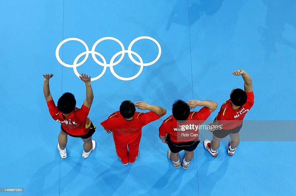 Ma Long (R), Wang Hao (2nd R), Coach Liu Guoliang (2nd L) and Zhang Jike (L) of China celebrate defeating Korea to win the Men's Team Table Tennis gold medal match on Day 12 of the London 2012 Olympic Games at ExCeL on August 8, 2012 in London, England.