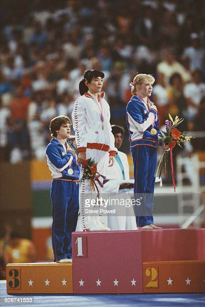 Ma Yanhong of China and Julianne McNamara of the United States both receive their gold medals in the Women's Uneven Bars event with Mary Lou Retton...