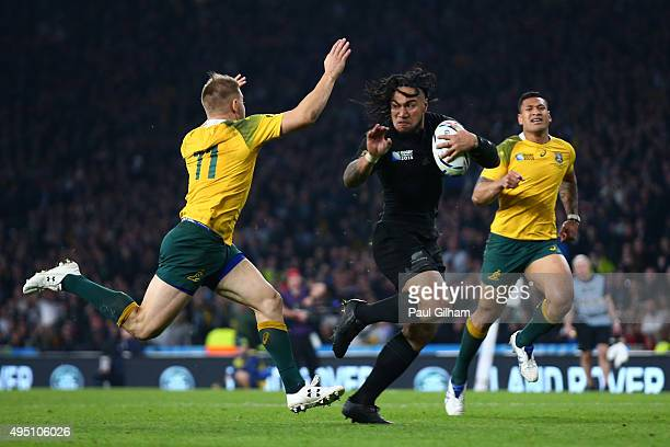 Ma'a Nonu of New Zealand hands off Drew Mitchell of Australia on the way to score his team's second try during the 2015 Rugby World Cup Final match...
