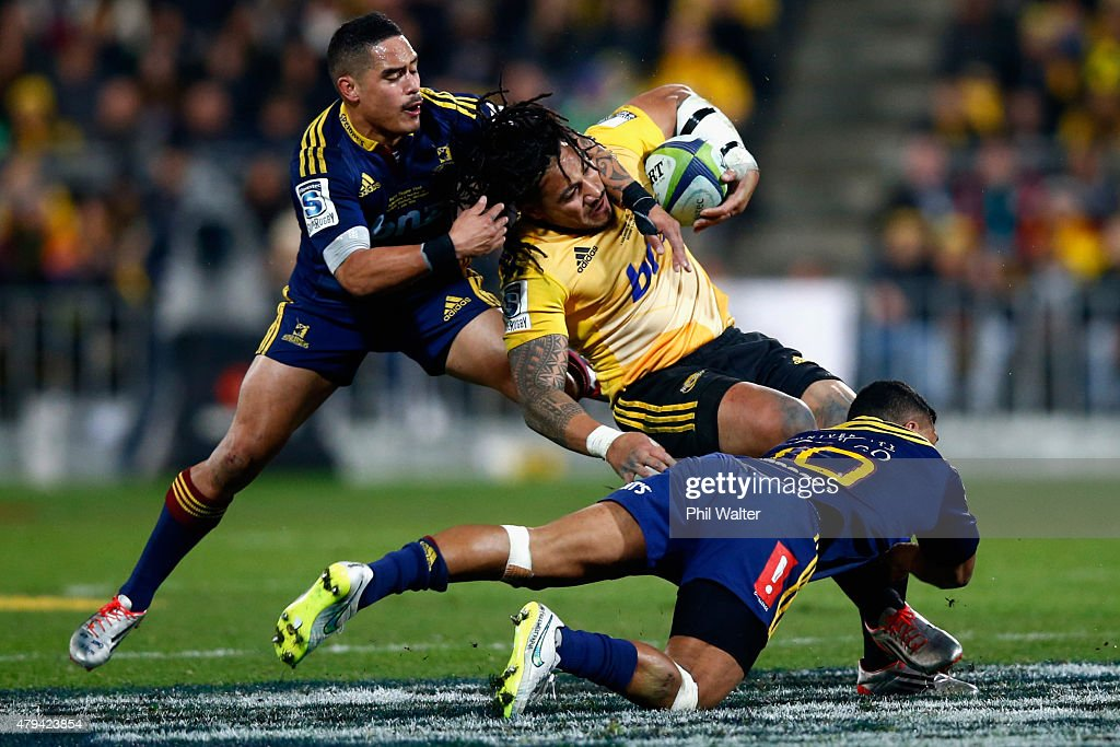 Ma'a Nonu of the Hurricanes is tackled by Aaron Smith and Lima Sopoaga of the Highlanders during the Super Rugby Final match between the Hurricanes...