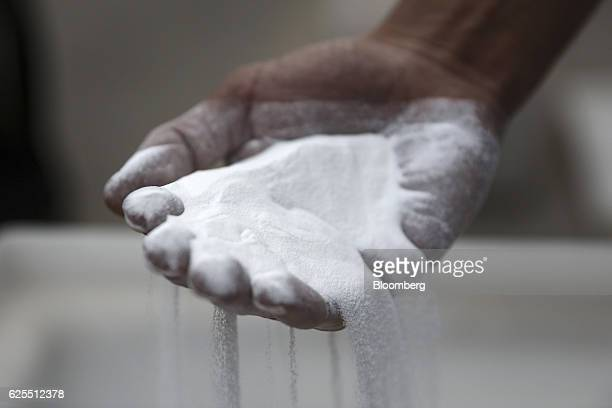 A Ma'aden worker holds a handful of processed alumina inside the aluminium plant at the Ras Al Khair Industrial City operated by the Saudi Arabian...