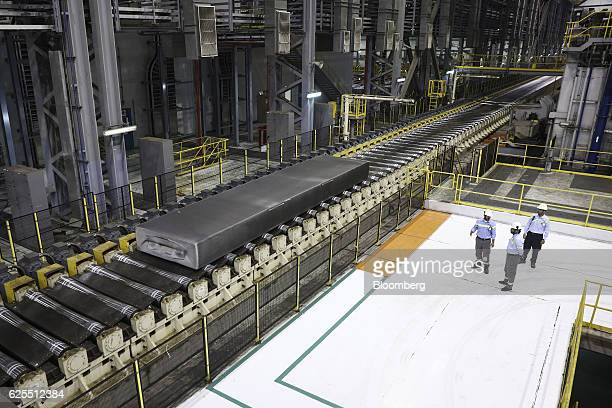 Ma'aden workers stand and watch as section of aluminium moves along the aluminium rolling mill at the Ras Al Khair Industrial City operated by the...