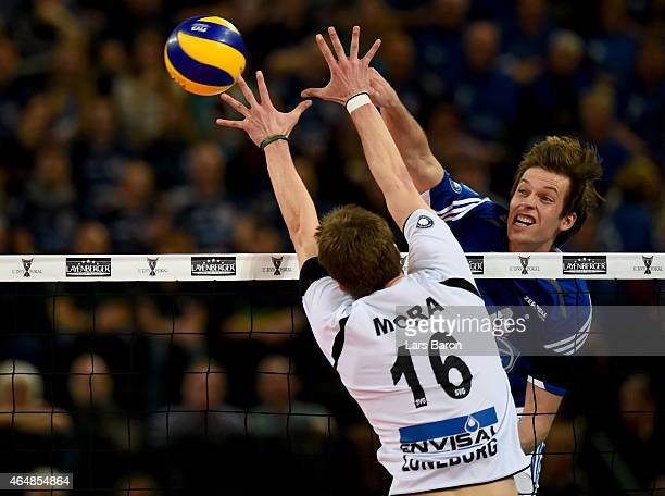 Maarten van Garderen of Friedrichshafen hits the ball next to Carlos Mora Sabate of Lueneburg during the German Men Cup Final between SVG Lueneburg...