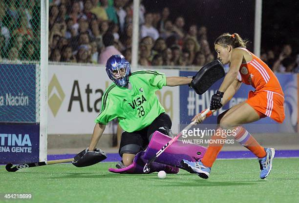 Maartje Paumen of the Netherlands dribbles the ball before scoring a goal against Argentina's goalkeeper Belen Succi during the shootout in their...