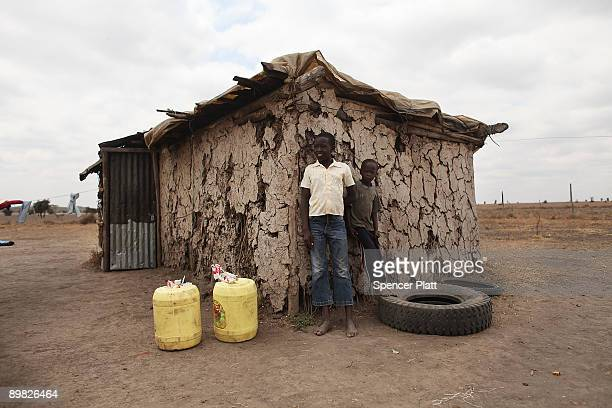 Maasai children stand next to their home with two jerry cans of water which were delivered to them by a neighbor after their mother passed away on...