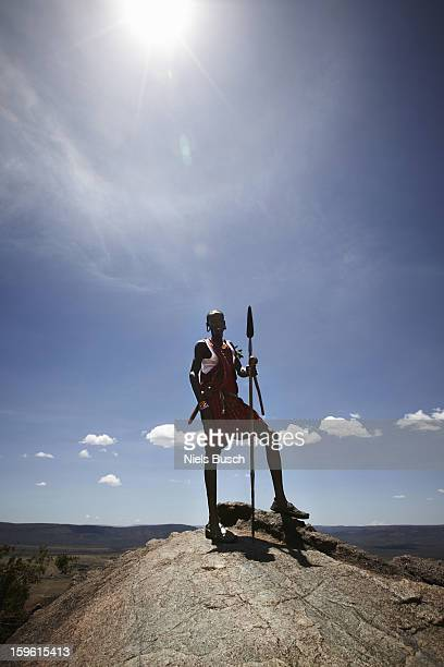 Maasai man standing on top of rock
