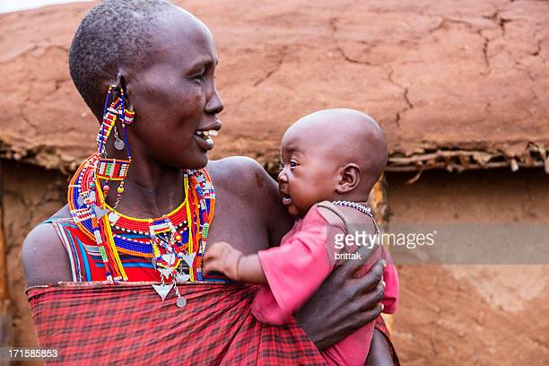 Maasai mother and child outside dung hut.