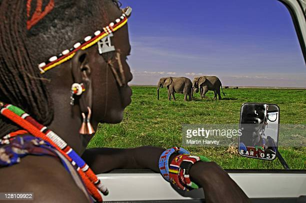 Maasai people. Maasai guide, Peter Kilea, in vehicle looking at elephant. Near Amboseli National Park Kenya