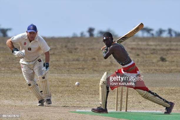 A Maasai warrior bats against a bowler from the British Army Training Unit Kenya team on June 18 2017 during a cricket tournament played in the wilds...