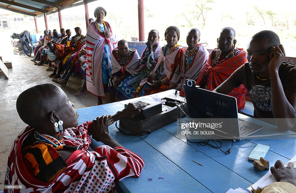Maasai woman registers to vote for the general elections scheduled for March 2013 in the village of Olgumi in Kajiado County West on December 18, 2012. Today marked the last day for Kenyans to register to vote and voter registration centres across the country saw a marked increase in attendance of voters who were desperate to register at the last minute. The Independent Electoral and Boundaries Commission (IEBC) has taken biometric computer equipment to populations in remote tribal areas in order to ensure that the chance of voting fraud is decreased for the country's forthcoming elections. AFP PHOTO/Carl de Souza
