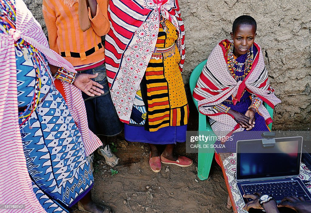 A Maasai woman sits in front of a laptop as she registers to vote in the village of Ewuaso Kedong in Kaijado County West on December 6, 2012. The Independent Electoral and Boundaries Commission (IEBC) has taken biometric computer equipment to populations in remote tribal areas in order to ensure that the chance of voting fraud is decreased for the country's forthcoming elections in March 2013. AFP PHOTO/Carl de Souza