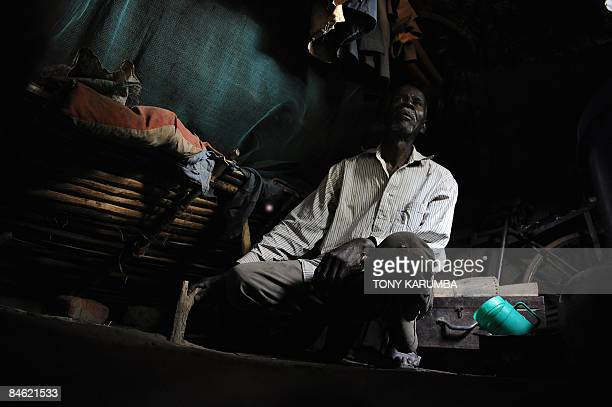 Mabula crouches beside his bed January 25 2009 in his mudthatched bedroom in a village near Mwanza under which is the grave of his granddaughter...