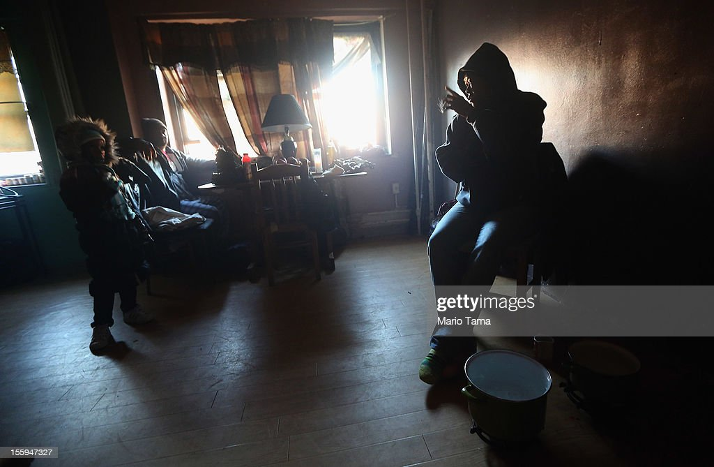Mac Baker (R) sits near niece Nytaisha Baker (L) next to pots of water she heats on the floor with small flames for a bit of warmth in her unheated apartment without electricity in the Ocean Bay public housing projects in the Far Rockaway neighborhood on November 9, 2012 in the Queens borough of New York City. Hundreds of Ocean Bay residents remain without heat or electricity eleven days after Superstorm Sandy struck. 53 New York City public housing buildings remain without power and 113 public housing buildings still don't have heat in the wake of the storm.