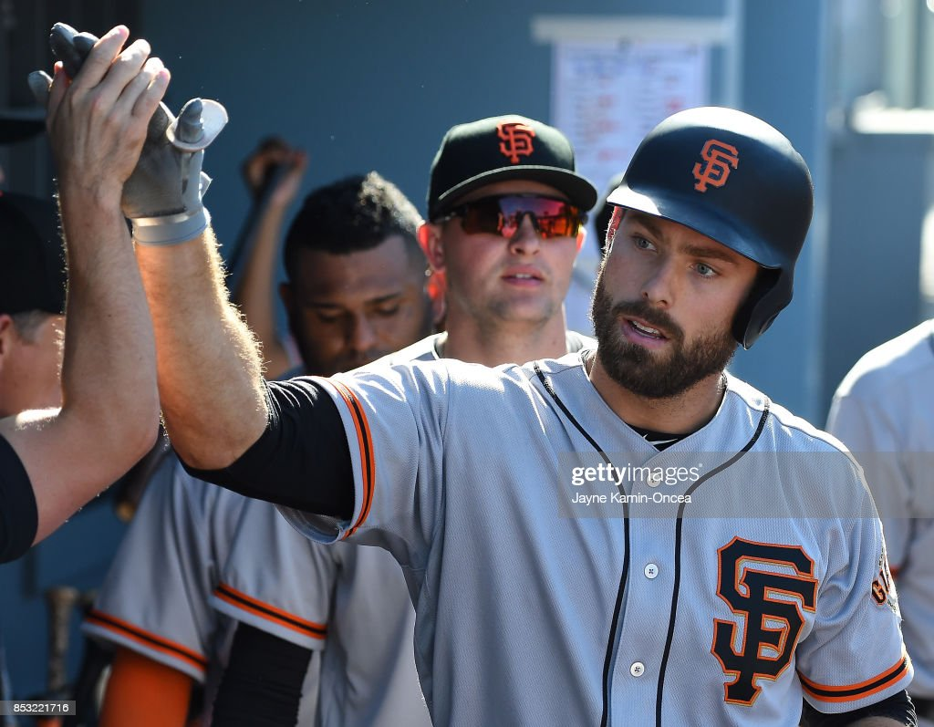 Mac Williamson #51 of the San Francisco Giants is greeted in the dugout after a solo home run in the eighth inning of the game against the Los Angeles Dodgers at Dodger Stadium on September 24, 2017 in Los Angeles, California.