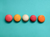 Five sweet and colorful macaroons or macaron on turquoise background French dessert Trendy bright photo background with space for text