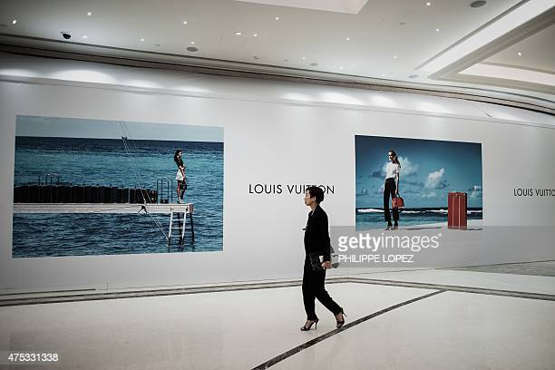 Macaugamblingeconomy FOCUS by Laura Mannering and Aaron Tam This picture taken on May 27 a woman walk past billboards of luxury shops to be opened in...