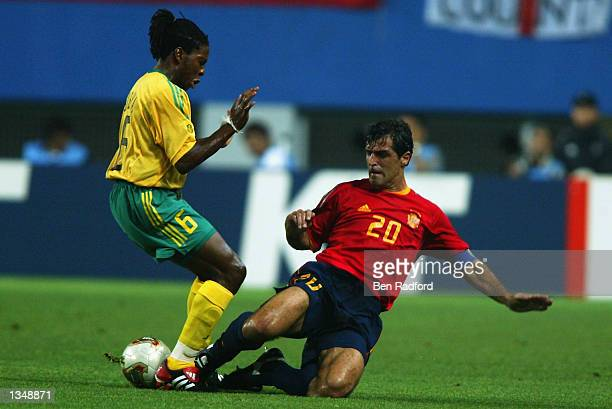 MacBeth Sibaya of South Africa is tackled by Miguel Angel Nadal of Spain during the Spain v South Africa Group B World Cup Group Stage match played...