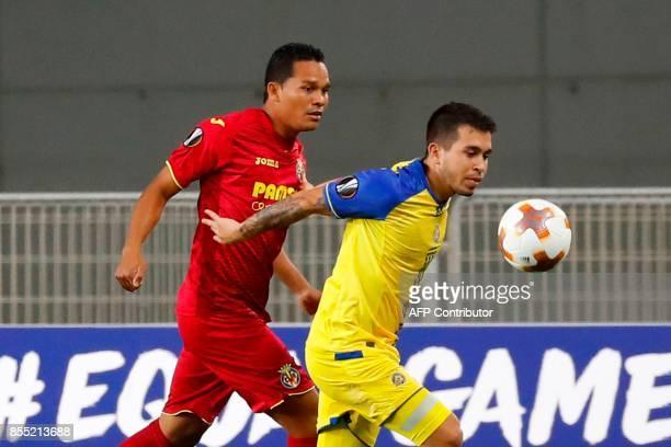 Maccabi's Italian midfielder Cristian Battocchio vies for the ball against Villareal's Colombian forward Carlos Bacca during the UEFA Europa League...