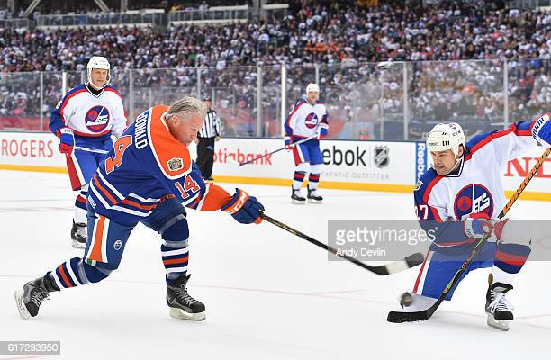 J MacDonald of the Edmonton Oilers alumni fires a shot with pressure from Teppo Numminen of the Winnipeg Jets alumni during the 2016 Tim Hortons NHL...