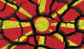Macedonia flag painted on cracked earth background.
