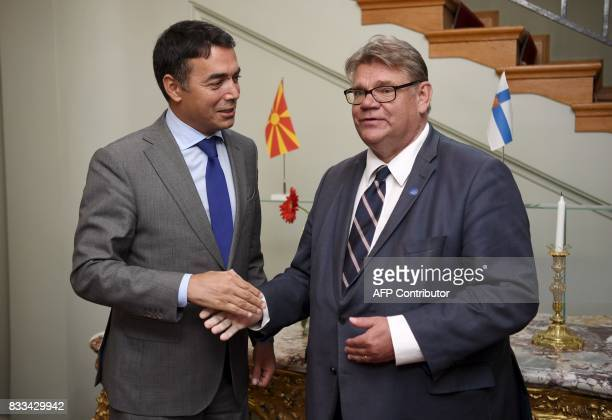 Macedonian Foreign Minister Nikola Dimitrov and Finnish counterpart Timo Soini shake hands during a visit in Helsinki Finland on August 17 2017 / AFP...
