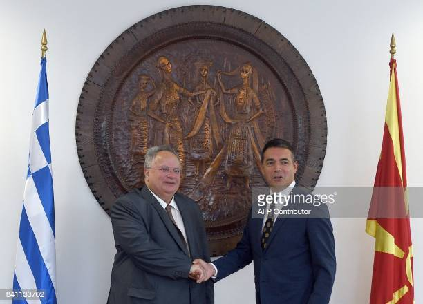 Macedonian Minister of Foreign Affairs Nikola Dimitrov shakes hands with Greek counterpart Nikos Kotzias during a welcoming ceremony at the Ministry...