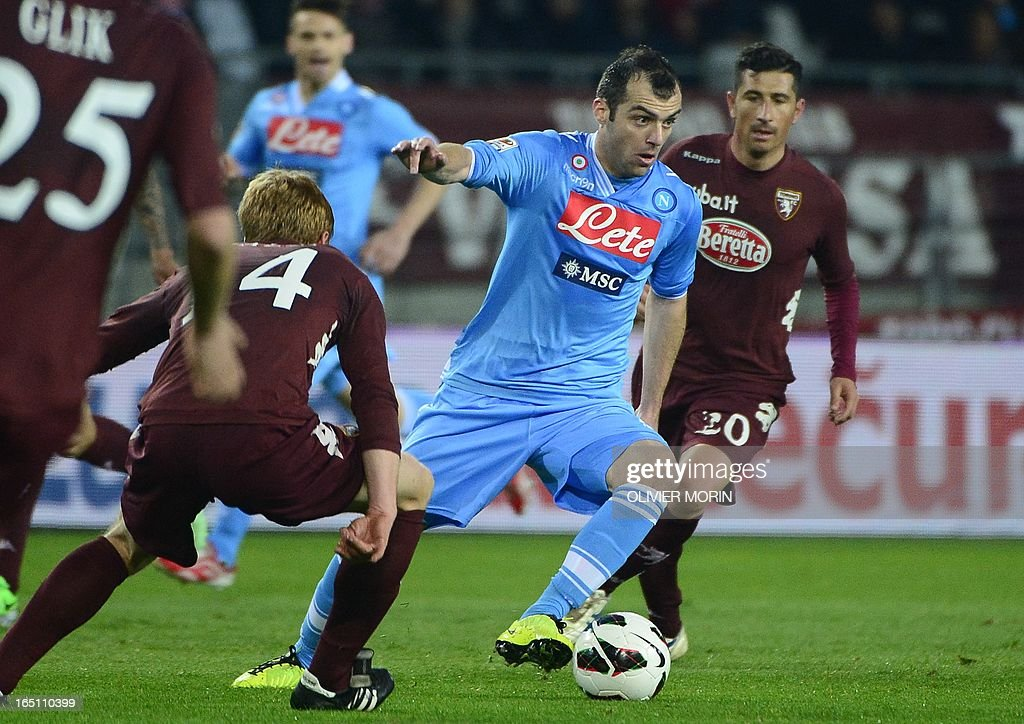 Macedonian Napoli's striker Goran Pandev (R) fights for the ball with Torino's Swiss midfielder Migjen Basha during the serie A football match between Turin and Naples, on March 30, 2013 in Turin, at the Olympic stadium .