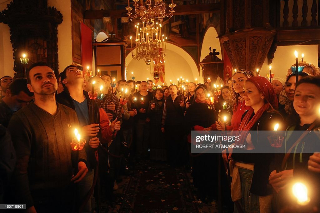 Macedonian Orthodox Christians hold candles as they take part in a midnight Easter service at the Saint Jovan Bigorski monastery, in Mavrovo, some 145 km west from the capital Skopje, in Macedonia, early on April 20, 2014.The Macedonian Orthodox Church celebrated Easter, according to the Julian calendar. AFP PHOTO / ROBERT ATANASOVSKI