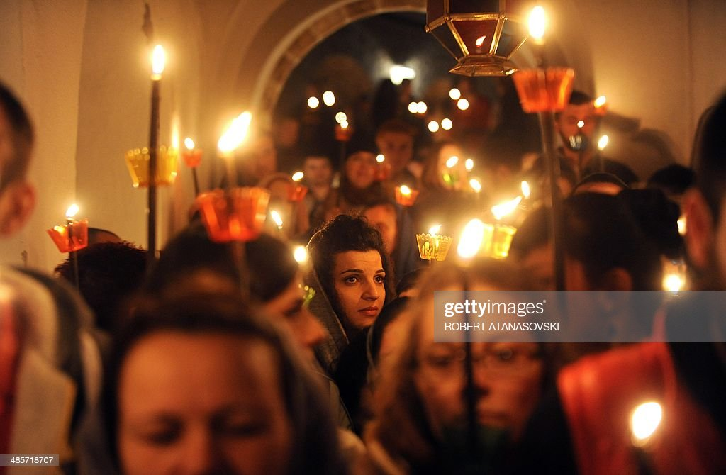 Macedonian Orthodox Christians hold candles lit from the holy fire that arrived from Jerusalem during an Easter service at the Saint Jovan Bigorski monastery, in Mavrovo, some 145 km west from the capital Skopje, in Macedonia, on April 20, 2014.The Macedonian Orthodox Church celebrated Easter, according to the Julian calendar.