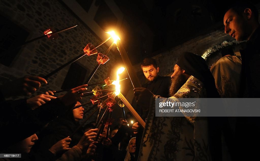 Macedonian Orthodox Christians light candles from the holy fire that arrived from Jerusalem during an Easter service at the Saint Jovan Bigorski monastery, some 145 km west from the capital Skopje, in Macedonia, on April 20, 2014.The Macedonian Orthodox Church celebrated Easter, according to the Julian calendar.