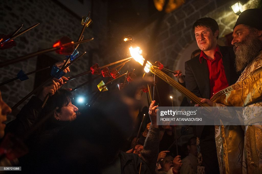 Macedonian Orthodox light candles from the holy fire that arrived from Jerusalem during Easter services at the St. Jovan Bigorski monastery, some 145 km west of the capital Skopje, on May 1, 2016. The Macedonian Orthodox Church celebrated Easter, according to the Julian calendar. / AFP / ROBERT