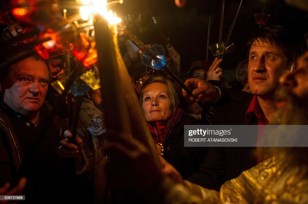 Macedonian Orthodox light candles from the holy fire that arrived from Jerusalem during Easter services at the St. Jovan Bigorski monastery, some 145 km west from the capital Skopje, on May 1, 2016. The Macedonian Orthodox Church celebrates Easter according to the Julian calendar. / AFP / ROBERT