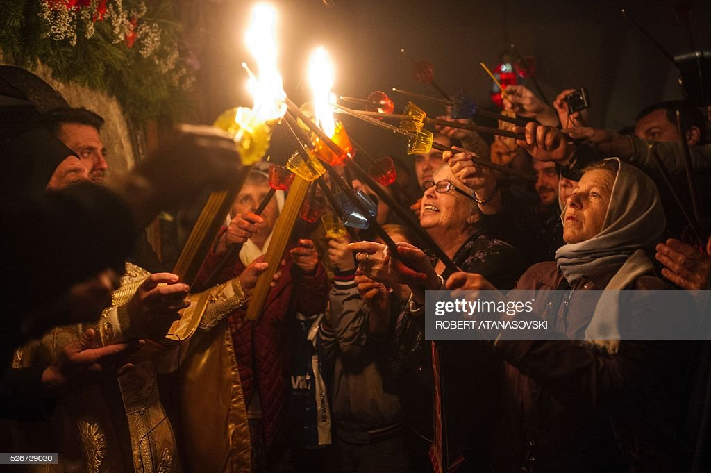 Macedonian Orthodox light candles from the holy fire that arrived from Jerusalem during Easter services at the St. Jovan Bigorski monastery some 145 km west from the capital Skopje, on May 1, 2016. The Macedonian Orthodox Church celebrate Easter according to the Julian calendar. / AFP / ROBERT