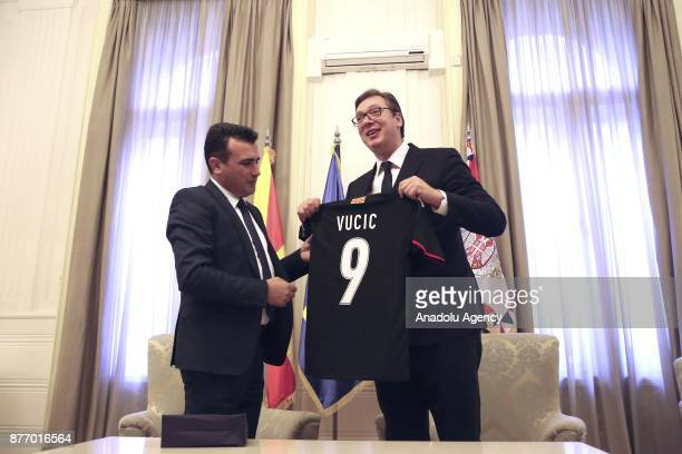Macedonian Prime Minister Zoran Zaev presents a jersey to President of Serbia Aleksandar Vucic with his name written on during their meeting in...