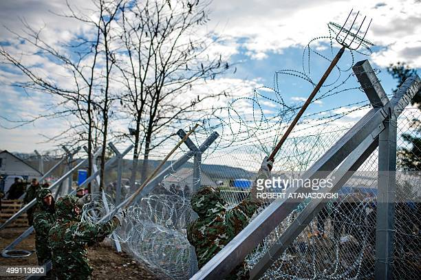 Macedonian soldiers build a border fence to prevent illegal crossings by migrants on the GreekMacedonian border near Gevgelija on November 29 2015A...