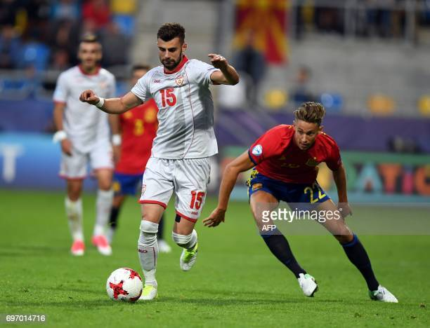 Macedonia's defender Egzon Bejtulai and Spain's midfielder Marcos Llorente vie for the ball during the UEFA U21 European Championship Group B...
