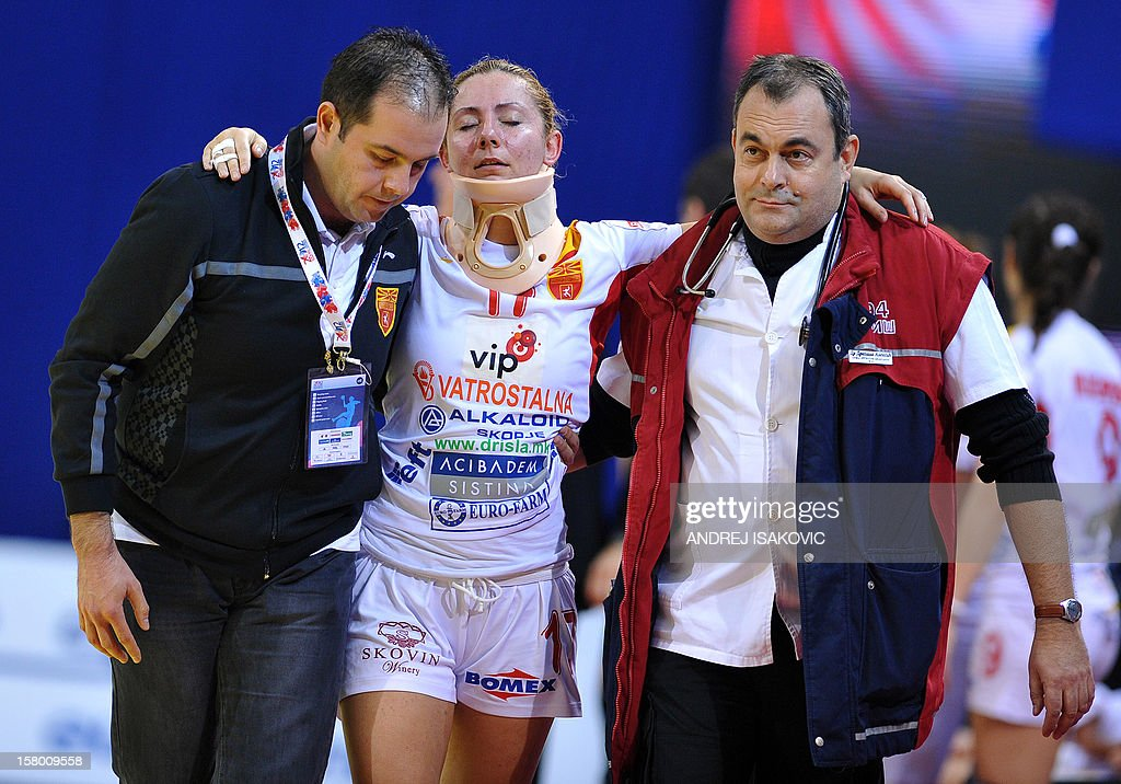 Macedonia's Dragana Pecevska (C) is helped off the pitch after an injury on December 8, 2012 during a women's EHF European Handball Championship match at the Hall Cair in Nis. AFP PHOTO / ANDREJ ISAKOVIC