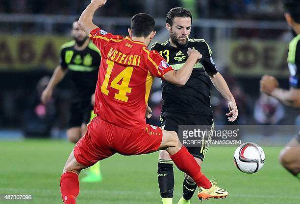 FYR Macedonia's Kire Ristevski vies with Spain's Juan Mata during the Euro 2016 Group D qualifying football match between FYR Macedonia and Spain at...