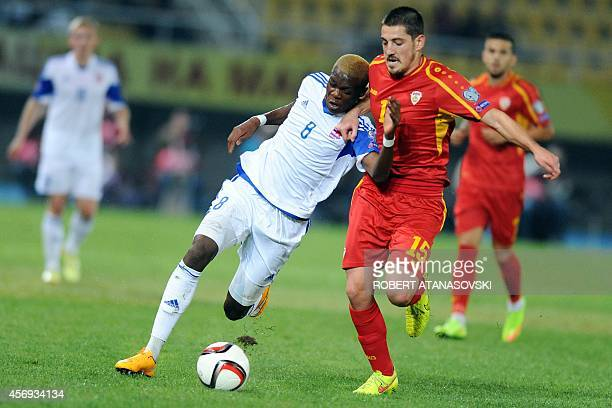 Macedonia's midfielder Arijan Ademi vies with Luxembourg 's defender Christopher Martins Pereira during the Euro 2016 group D qualifying football...