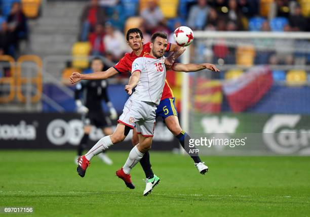 Macedonia's stricker Viktor Angelov and Spain's midfielder Marcos Llorente vie for the ball during the UEFA U21 European Championship Group B...