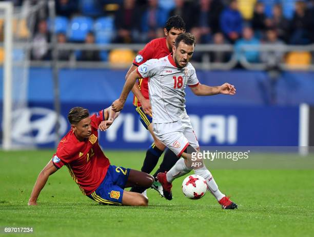 Macedonia's stricker Viktor Angelov is tackled by Spain's midfielder Marcos Llorente during the UEFA U21 European Championship Group B football match...